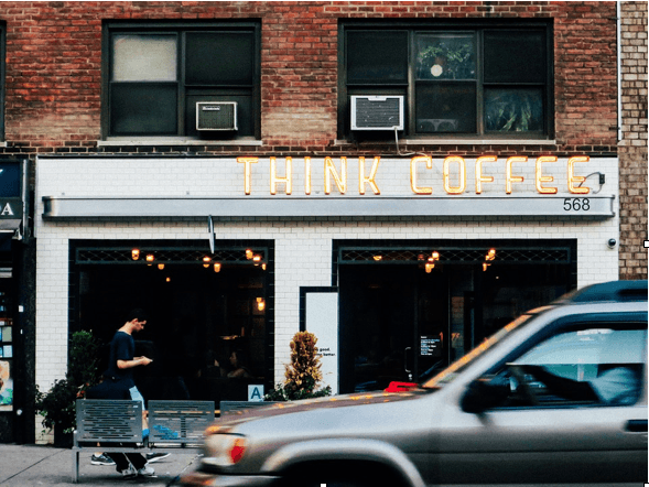 A coffee shop with a bright sign on a street