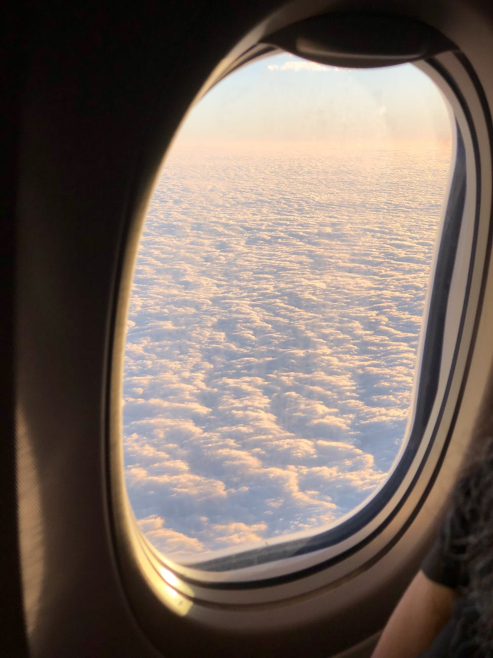 fluffy clouds though airplane window during flight