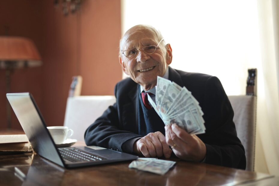 happy senior businessman holding money in hand while working on laptop at table